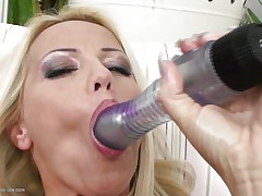 Blonde milf wearing only a pair of sexy black nylons is playing solo with her large dildo, that honey sucks it and the fills her shaved vagina with it, fucking herself as hard as that honey can but that is not enough. Luckily her brunette girlfriend is willing to aid and gives her a hand, rubbing her muff and then fingering it, want to see what else she's willing to do?