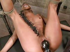 With her feet fastened up and metal clamps all over her body the ebony slut endures a harsh punishment. This mistress knows what he's doing and gives her both pang and pleasure. She can't even scream as her throat is folded with scotch tape. Look at that shaved pussy and how unfathomable she's rubbing it with the vibrator.